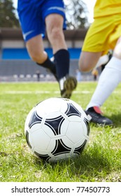 Image of soccer ball in green grass with footballers legs on background