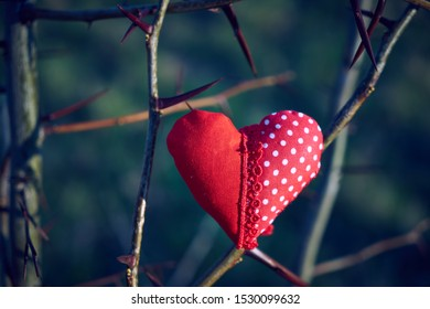 An image of a soft toy in the shape of a heart. Handicraft work.