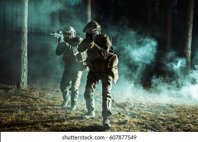 Image of soldiers in the smoke moving in battle operation. Back light, dark night, forest