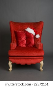An image of a solitary bright red chair with a santa hat
