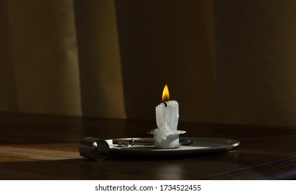 Image of a solitary burning candle in candlestick holder