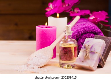 Image of spa concept with flowers, candles, sea salt, oil, towel and natural bar of soap