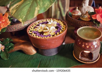 Image of spa therapy, flowers in water, on a bamboo mat