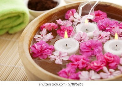 Image of spa therapy, flowers in water, on a bamboo mat.