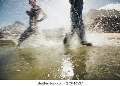 Image of splashes of water while triathletes running in lake.  Athletes training for triathlon race.