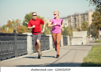 Image of sport couple running along promenade