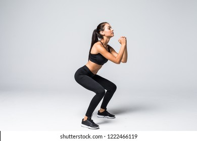 Image of sporty athletic woman in sneakers and tracksuit squatting doing sit-ups in gym isolated over gray background