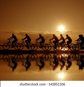 Image of sporty company friends on bicycles outdoors against sunset. Silhouette A lot phases of motion of a single cyclist along the shoreline coast Reflection on water Space for iscription