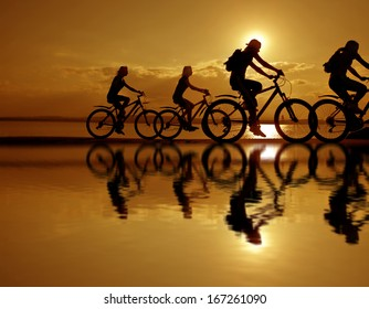 Image of sporty company friends on bicycles outdoors against sunset. Silhouette A lot phases of motion of four 4 cyclist along  shoreline coast Reflection sun on water Copy Space for inscription