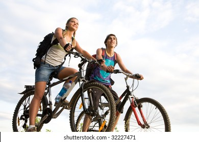 Image of sporty couple on bicycles outdoors looking somewhere with smiles