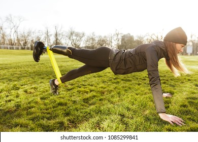 Image of sporty handicapped woman in black tracksuit warming up and doing plank with prosthesis leg on nature using rubber band