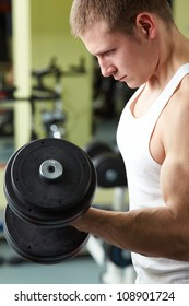 Image of sporty man training in gym with barbell