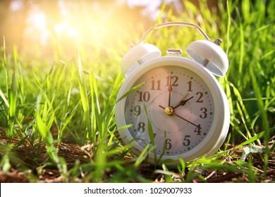 Image of spring Time Change. Summer back concept. Vintage alarm Clock outdoors