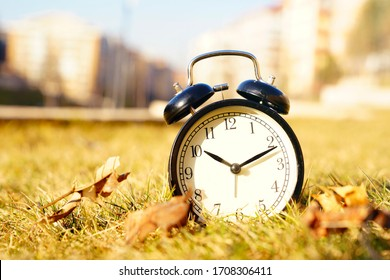 Image of spring Time Change. Summer back concept. Vintage alarm Clock outdoors. alarm clock on green grass