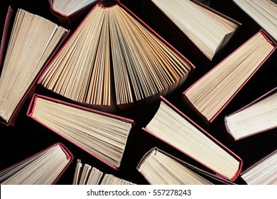 image of a stack of hard back books on the end of the pages toned with a retro vintage warm filter, vintage books  background