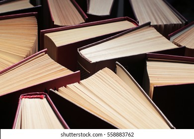 image of a stack of hard back books on the end of the pages toned with a retro vintage warm like filter, vintage books background