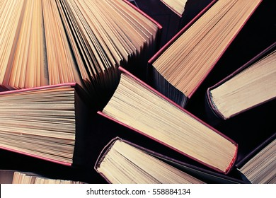 image of a stack of hard back books on the end of the pages toned with a retro vintage warm instagram like filter app or action effect, vintage books background