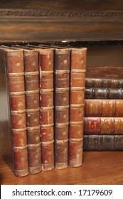 An image of stacks of antique books