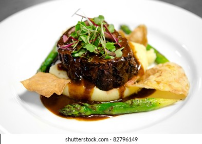 Image of a steak fillet on a bed of mashed potatoes with asparagus, chips and gravy