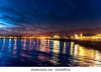 Image of Stearns Wharf at night in Santa Barbara California shows the brilliant lights of a lively city destination.