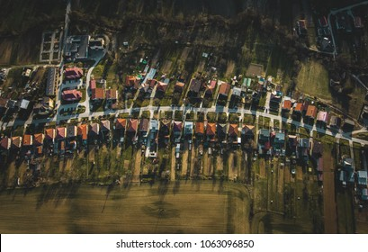 Image of street in (Europe - Slovakia) with a lot of houses in a row in springtime. Street full of houses near the field green meadows and forest. Street from above with stream and many trees.
