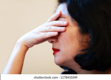 Image of stressed woman face palm or cover her face by hands sit by wall.4os Asian woman depressed or crying or she may suffering from headaches and migraine as of Menopause or get trouble in her life