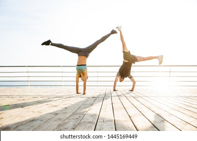 Image of strong two young sports woman and man friends loving couple at the beach near sea make cartwheel exercise.
