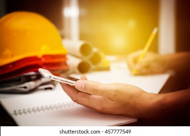 Image of structure engineer holding mobile smartphone calculate value in his product and drawing a building blueprint, hipster view vintage of photography.