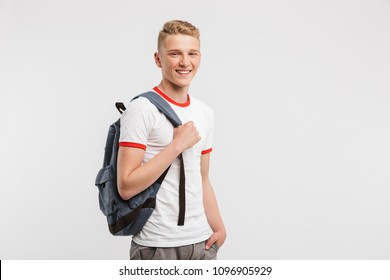Image of student boy having clean healthy skin wearing casual clothing and backpack smiling at camera isolated over white background