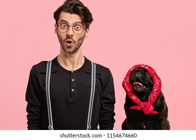 Image of stupefied young male photographer in fashionable clothes, poses together with his lovely pet at camera, isolated over pink background. Black pedigree dog wears stylish red bandana on head.