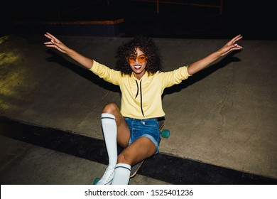 Image of stylish african american girl in streetwear smiling and riding on skateboard at night outdoors