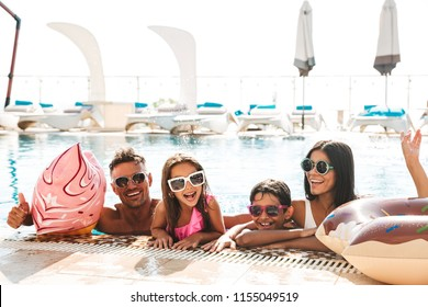 Image of stylish happy family with children wearing sunglasses swimming in pool with rubber ring outside hotel