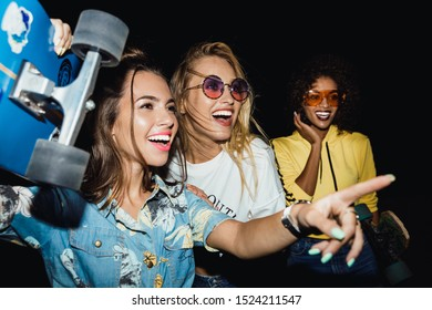 Image of stylish multinational girls in streetwear smiling and holding skateboards at night walk outdoors