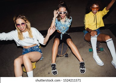 Image of stylish multinational girls in streetwear smiling and riding on skateboards at night party outdoors