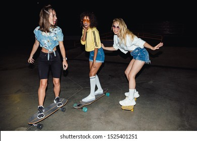 Image of stylish multinational girls in streetwear smiling and riding skateboards at night outdoors