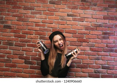 Image of subcultural hip hop girl 20s standing against brick wall with spray cans