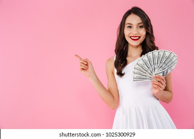 Image of successful asian woman 20s holding fan of money in dollar cash and pointing finger aside on copyspace with smile isolated over pink background