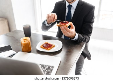 Image of successful businessman 30s in formal suit having breakfast while working on laptop in bright office