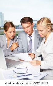 Image of successful businesspeople looking at document while discussing it in office