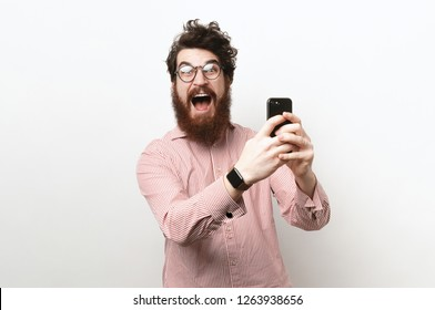 Image of suprised earded man with glasses and culry-hair, over white background