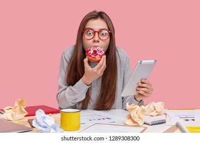 Image of surprised brunette woman in transparent spectacles, holds touchpad, surfes internet eats delicious doughnut, dressed in casual clothes, works with papers, isolated on pink background