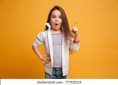 Image of surprised little girl child standing isolated over yellow background. Looking camera have an idea.