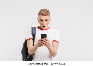 Image of surprised male student having clean healthy skin wearing backpack chatting on mobile phone isolated over white background