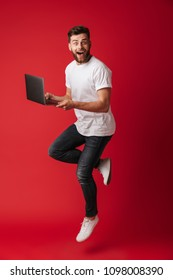 Image of surprised young man jumping isolated over red wall background using laptop computer. Looking camera.