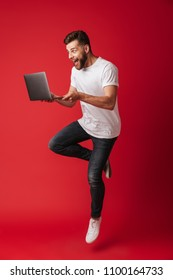 Image of surprised young man jumping isolated over red wall background using laptop computer.