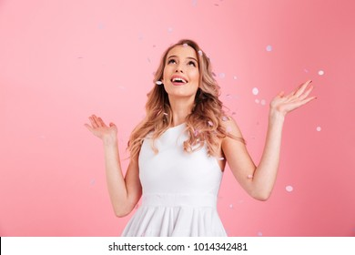 Image of surprised young woman standing isolated over pink background over confetti. Looking aside.