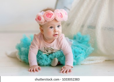 Image of sweet adorable baby girl in a wreath of pink roses, closeup portrait of cute 8 month-old smiling girl,  beautiful toddler.