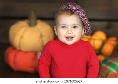Image of sweet baby girl in the studio. Photo shoot theme of autumn, pumpkin, vegetables, harvest. Closeup portrait of cute 8 month-old smiling girl,  toddler.