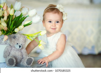 Image of sweet baby girl in a wreath, closeup portrait of cute 8 month-old smiling girl in studio with teddy bear, toddler.