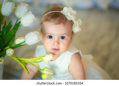 Image of sweet baby girl in a wreath, closeup portrait of cute 8 month-old smiling girl in studio, toddler.